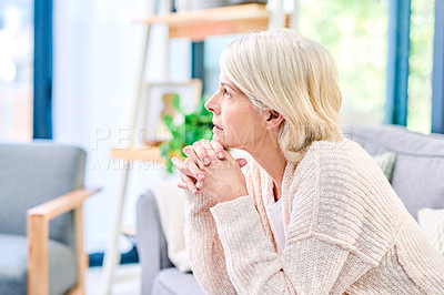 Buy stock photo Shot of a senior woman looking thoughtful on the sofa at home