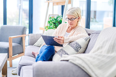 Buy stock photo Shot of a senior woman using a digital tablet on the sofa at home