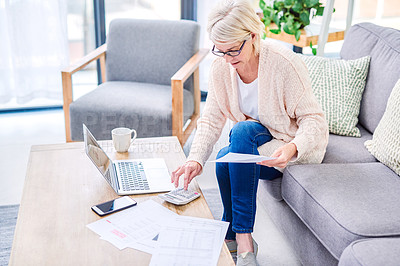Buy stock photo Shot of a senior woman using a laptop and calculator while going through paperwork at home