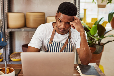 Buy stock photo Shot of a stressed young man using a laptop while working in a ceramic studio