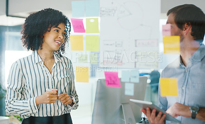 Buy stock photo Shot of a young businessman and businesswoman using a digital tablet while having a brainstorming session in a modern office