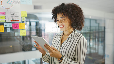 Buy stock photo Shot of a young businesswoman using a digital tablet while having a brainstorming session in a modern office