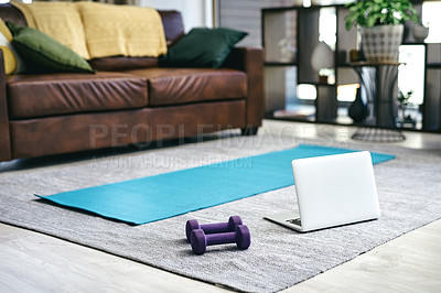 Buy stock photo Closeup shot of dumbbells and a laptop alongside an exercise mat on the floor at home
