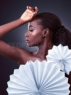 Buy stock photo Studio shot of a beautiful young woman posing with origami fans against a black background