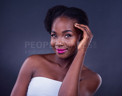 Buy stock photo Studio portrait of a beautiful young woman posing against a black background