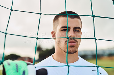 Buy stock photo Shot of a goalkeeper standing behind the net