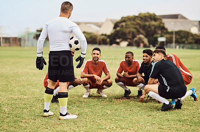 Buy stock photo Shot of a team of soccer players having a discussion on the field