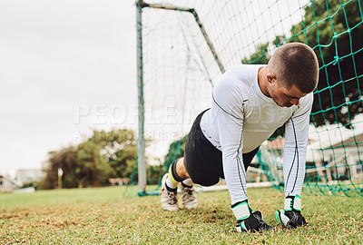 Buy stock photo Shot of a goalkeeper doing push-ups on the field