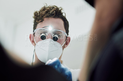 Buy stock photo Shot of a young man performing a dental procedure on a patient