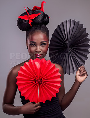 Buy stock photo Studio portrait of a beautiful young woman wearing Asian inspired makeup and posing with origami against a grey background