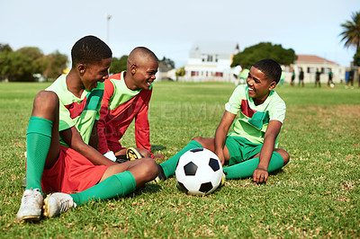 Buy stock photo Shot of a group of young boys taking a break while playing soccer on a sports field