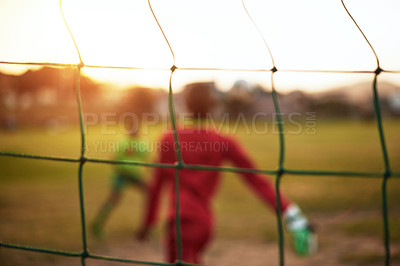 Buy stock photo Defocused shot of young boys playing soccer on a sports field