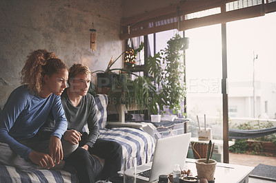 Buy stock photo Shot of a young couple using a laptop on the sofa at home