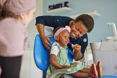 Buy stock photo Shot of a young woman brushing her adorable daughter's teeth in a dentist's chair