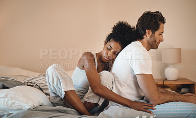 Buy stock photo Shot of a woman embracing her husband from behind while sitting in their bedroom
