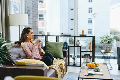 Buy stock photo Shot of a young woman wearing earphones while sitting at home with a cup of coffee