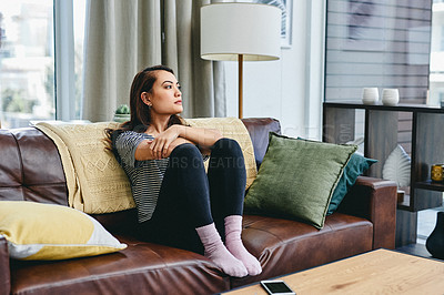 Buy stock photo Shot of a young woman sitting on the couch at home