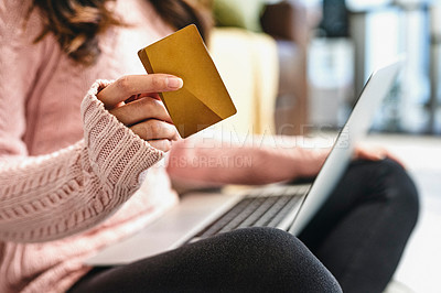 Buy stock photo Shot of a woman holding her credit card while sitting at home with her laptop