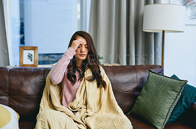 Buy stock photo Shot of a young woman suffering with a headache while sitting at home