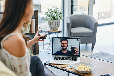 Buy stock photo Shot of a woman sharing a toast with her boyfriend while doing a video call