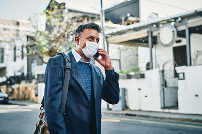 Buy stock photo Shot of a masked businessman using a smartphone against a city background