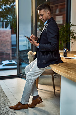 Buy stock photo Shot of a confident businessman using a digital tablet in a modern office