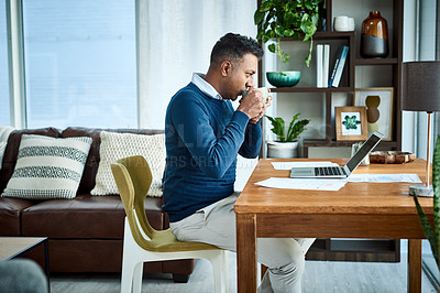 Buy stock photo Shot of a businessman using a laptop and having coffee while working from home