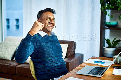 Buy stock photo Shot of a happy businessman using a laptop and headset while working from home