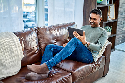Buy stock photo Shot of a man using a digital tablet on the sofa at home