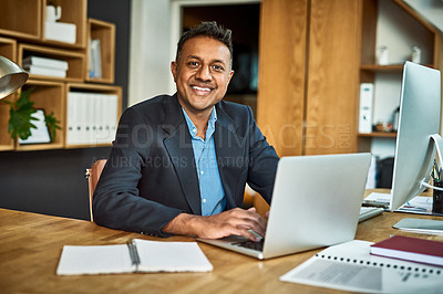 Buy stock photo Portrait of a confident businessman using a laptop at his desk in a modern office