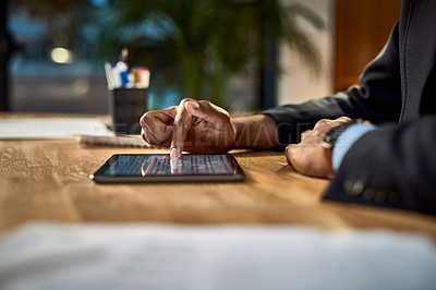 Buy stock photo Shot of an unrecognisable businessman using a digital tablet at his desk in a modern office