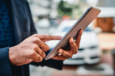 Buy stock photo Shot of a businessman using a digital tablet against a city background