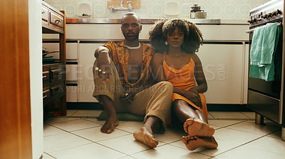 Buy stock photo Shot of a young couple sitting on the floor of the kitchen at home