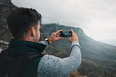 Buy stock photo Shot of a young man taking photos while out on a hike