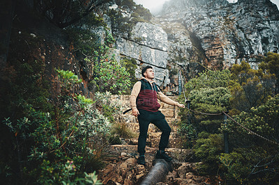 Buy stock photo Shot of a young man hiking through the mountains