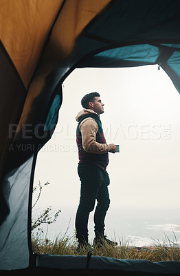 Buy stock photo Shot of a young man drinking coffee while camping in the wilderness