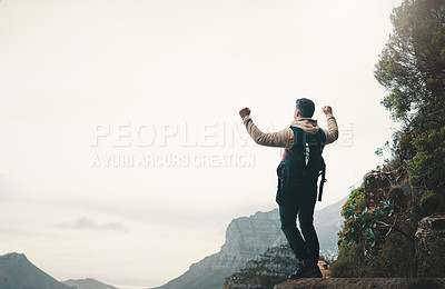 Buy stock photo Rearview shot of a young man standing with his arms outstretched while hiking on a mountain