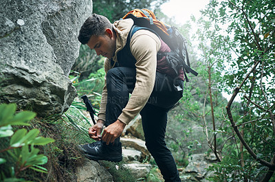 Buy stock photo Shot of a young man tying his laces while out on a hike