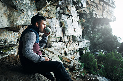 Buy stock photo Shot of a young man drinking coffee while hiking through the mountains