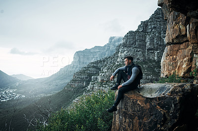 Buy stock photo Shot of a young man looking at the view while sitting on a mountain cliff