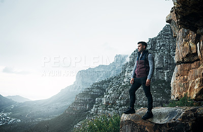 Buy stock photo Shot of a young man standing on a cliff while out on a hike