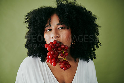 Buy stock photo Studio shot of a young woman eating a bunch of red grapes against a green background