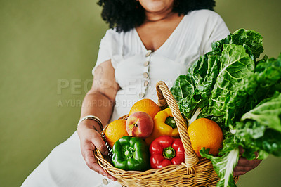 Buy stock photo Studio shot of a woman holding a basket of fresh fruit and vegetables against a green background