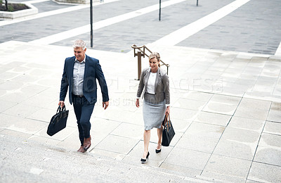 Buy stock photo Shot of two mature businesspeople walking up a staircase in the city