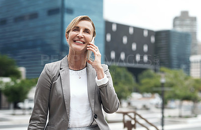 Buy stock photo Shot of a mature businesswoman talking on a cellphone in the city