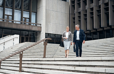 Buy stock photo Shot of two mature businesspeople having a discussion while walking down a staircase in the city