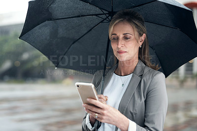 Buy stock photo Shot of a mature businesswoman using a cellphone and holding an umbrella while out in the city