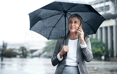 Buy stock photo Shot of a mature businesswoman talking on a cellphone and holding an umbrella while out in the city
