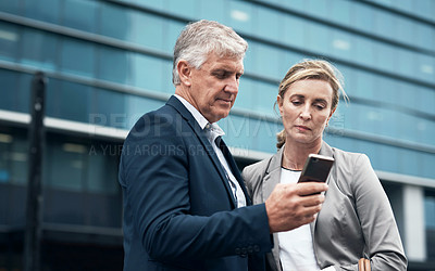 Buy stock photo Shot of two mature businesspeople looking at something on a cellphone together in the city