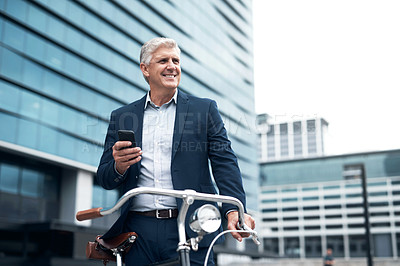 Buy stock photo Shot of a mature businessman using a cellphone while travelling on a bicycle in the city